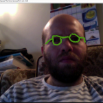 A screencap of a Google Hangout session with bright green spectacles drawn on my face.