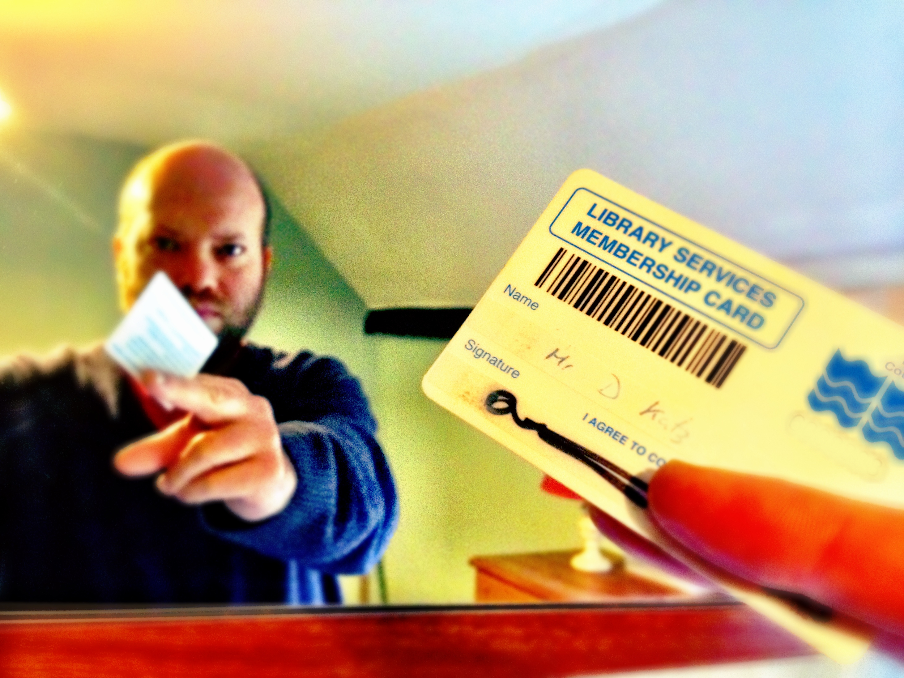 Me and my library card, reflected in a mirror.